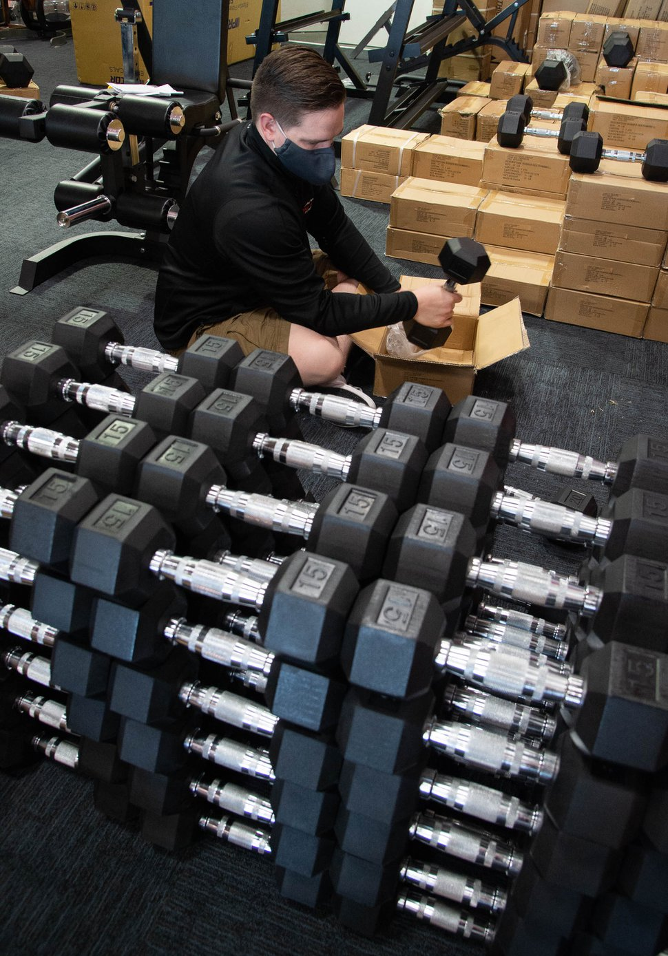 (Francisco Kjolseth | The Salt Lake Tribune) Chase Buckles, sales manager at Utah Home Fitness in Sandy, takes advantage of a slow moment to catch up on restocking inventory on Wednesday, Oct. 22, 2020.